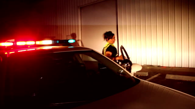 policewoman exits police car with flashing lights, runs - pursuit concept video stock e b–roll