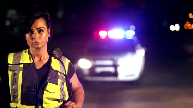 policewoman in front of car with emergency lights - rescue worker stock videos and b-roll footage