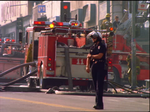 Policewoman in riot helmet standing in street with fire trucks in background / Los Angeles riots