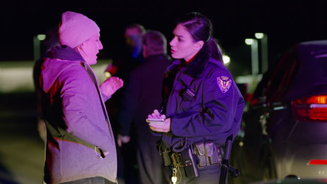 Policewoman interviewing woman at traffic accident at night / Eagle Mountain, Utah, United States