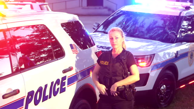 policewoman standing by police cars - police force stock videos & royalty-free footage