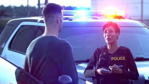 若い男と話す警官 - 犠牲者点の映像素材/bロール