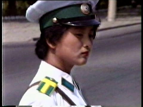 Policewoman turns in uniform manner to guide traffic Pyongyang Aug 88