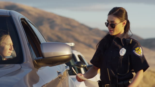 Policewoman walking from police car to give citation to driver at traffic stop / Eagle Mountain, Utah, United States