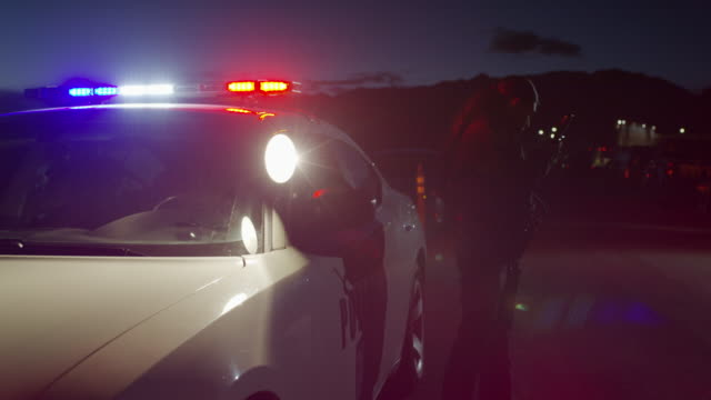 vídeos y material grabado en eventos de stock de policewoman walking from police car with lights flashing at night / eagle mountain, utah, united states - puerta del coche