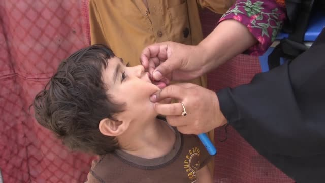 polio workers are accompanied by police as they administer vaccines in islamabad - asia stock videos & royalty-free footage