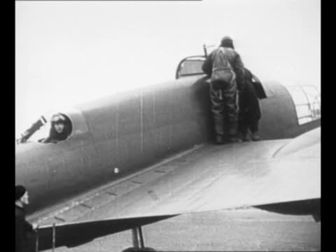 vídeos de stock e filmes b-roll de polish aviators approach as they come out of building / pilot sits in cockpit of military plane as crew gets into back / pilot takes weapons from men... - 1939