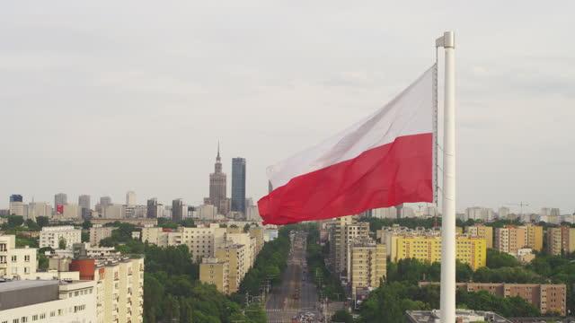 ワルシャワの市内中心部にある大きなラウンドアバウト交差点に立つポーランド国旗。ドローンビュー - ジャスパー国立公園点の映像素材/bロール