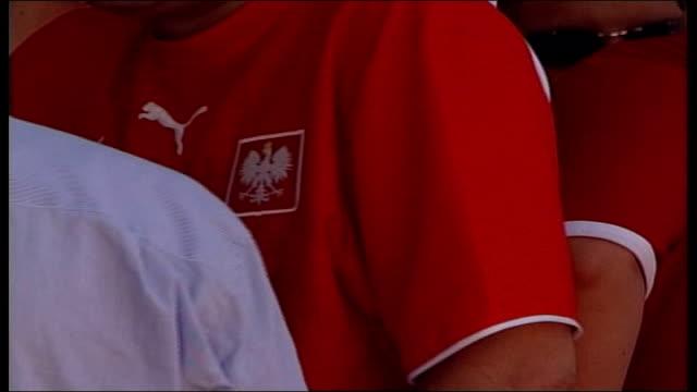 polish football hooligans; germany: dortmund: sequence polish fans wearing football shirts and caps milling about maciej woizniak talking with turton... - all shirts stock-videos und b-roll-filmmaterial