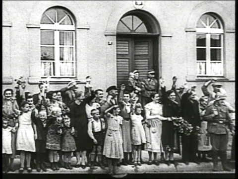 polish people standing outside building cheering waving at troops passing in cars pan waving crowd women children along street - poland stock videos & royalty-free footage