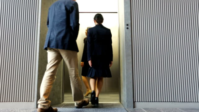 polite man sharing lift with japanese professional business women - social grace stock videos & royalty-free footage