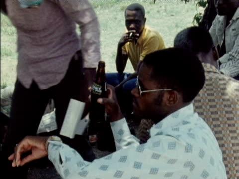 vidéos et rushes de political prisoners drink bottled beer underneath tree following their release from prison 1970s - indépendance