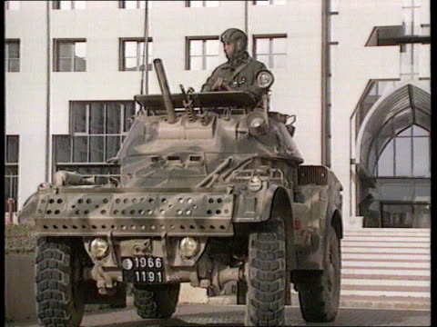 algiers ext ms soldiers in jeep by entrance to building cms soldier ms armoured car in road pull out by entrance to building ms people standing by... - アルジェリア点の映像素材/bロール