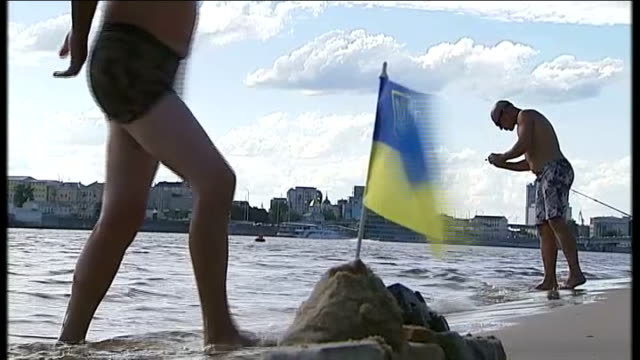 political tensions in ukraine; ukraine: kiev: ext england fans on beach singing 'god save the queen' and holding england flag sot three women wearing... - international team soccer stock videos & royalty-free footage