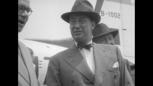 vidéos et rushes de us politician adlai stevenson ii posing for photo opportunity while talking to british official next to airplane after landing at hong kong airport... - adlai stevenson