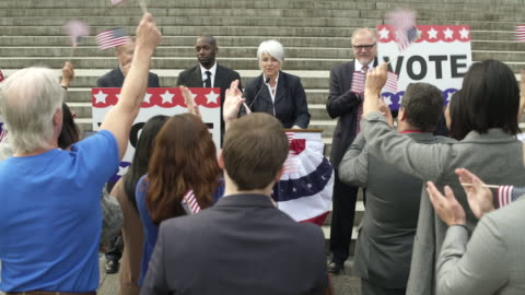 a politician giving a speech in front of an applauding crowd - uomo politico video stock e b–roll