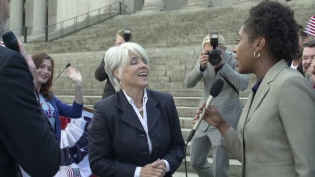 stockvideo's en b-roll-footage met a politician giving interviews while walking among her supporters - politieke bijeenkomst