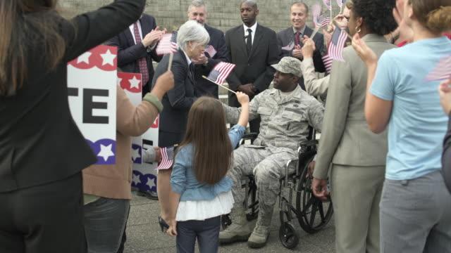 stockvideo's en b-roll-footage met a politician greeting a soldier sitting in a wheelchair - politieke bijeenkomst
