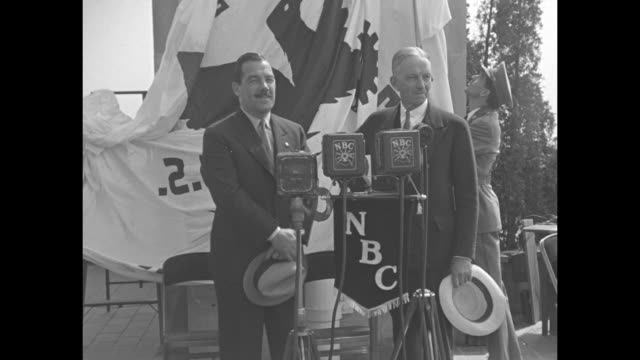 ms politician grover whalen stands with builder john r todd at nbc microphones as the nra flag is raised behind them / flag going up pole as people... - radio city music hall stock videos & royalty-free footage