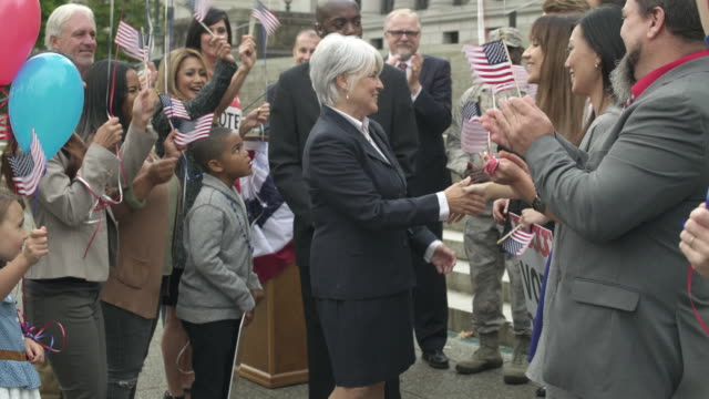 A politician shaking hands with her supporters
