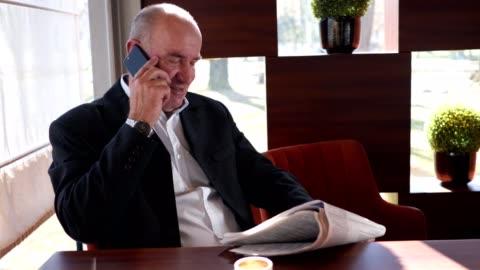 politico che parla al telefono e si rilassa in un bar - uomo politico video stock e b–roll