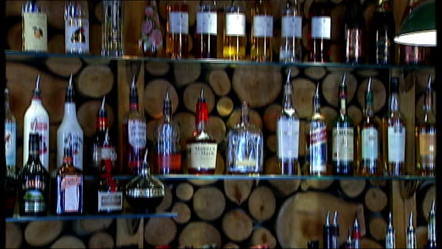 politicians dismiss minimum alcohol price plans to cut binge drinking; dates & locations unknown: int close shot of spirit bottles on shelf alcohol... - lager stock videos & royalty-free footage