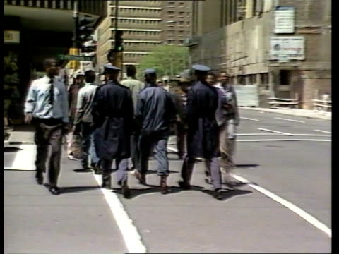 Politics AntiApartheid Protests Johannesburg BV Black police carrying batons up street MS Police on street corner RL TMS TRACK FORWARDS past riot...