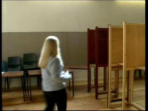 stockvideo's en b-roll-footage met local elections voting today lib lms 'polling station' poster on low fence woman into booth in polling station pan then puts voting slip in ballot box - stembus