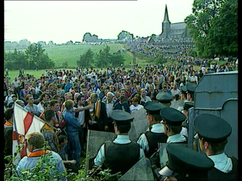 politics orange march to be rerouted july 1995 seq large crowd of orangemen facing ruc officers holding riot shields / missiles being thrown/ ruc... - kommode stock-videos und b-roll-filmmaterial