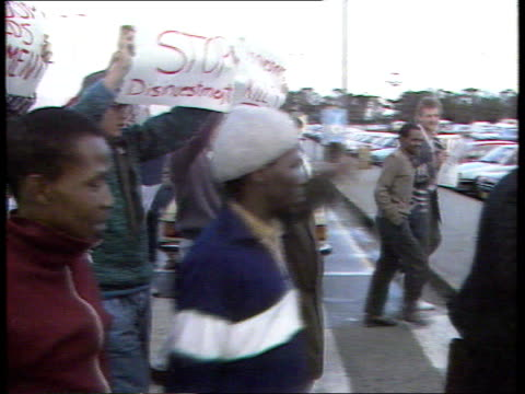 Politics Secret government payments to Inkatha EXT/1988 Airport MS Tutu towards with white man and black LIB MAT vicar as demos with banners round...