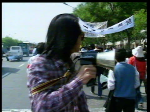 student riots china beijing university tgv students walking out though gate ms ditto ms students carrying banners walk out through gate towards ms... - communist party stock videos and b-roll footage
