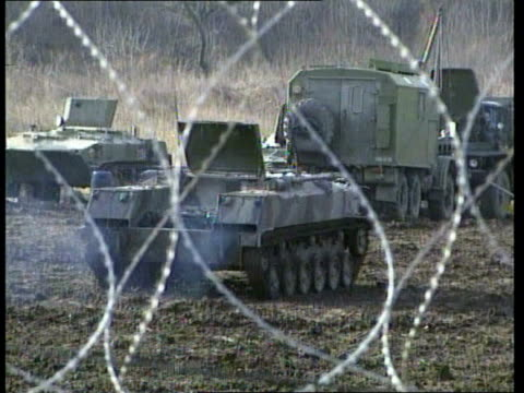 russia tightening grip on chechnya itn russian military truck along past gvs russian military vehicles in base compound seen through barbed wire ls... - military base stock videos & royalty-free footage