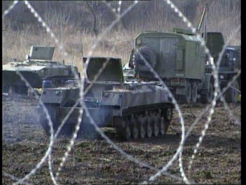 stockvideo's en b-roll-footage met russia tightening grip on chechnya itn russian military truck along past gvs russian military vehicles in base compound seen through barbed wire ls... - 1999