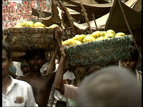 Tensions Straw Mission of Little Value LIB INDIA New Delhi EXT Traffic along street Men along street carrying fruit in baskets on their heads PULL...