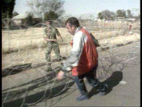 Politics/Crime AWB violence 1700 SOUTH AFRICA Ventersdorp MS SIDE plain clothes policeman and soldier pulling coils of barbed wire along RL LA Men on...