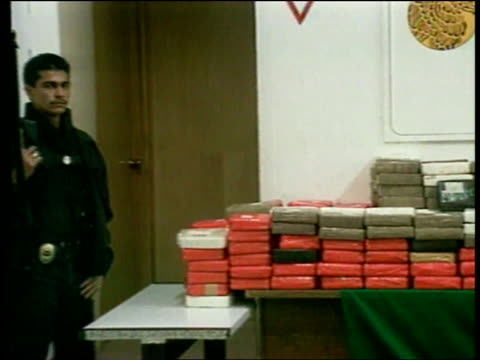 elections fuentes death itn mexico mexico city police officer guarding drugs haul zoom in packets of drugs stacked on table pan lr - sachet stock videos & royalty-free footage