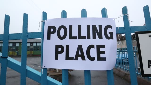 a polling place sign hangs on the gate of a polling station as voters arrive to cast their scottish independence referendum votes in edinburgh uk on... - 2014 scottish independence referendum stock videos & royalty-free footage
