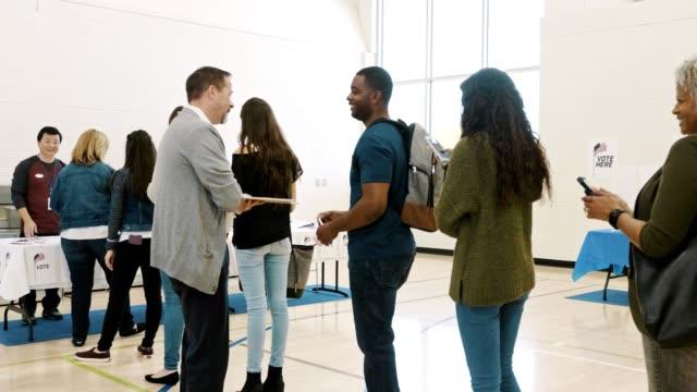 stockvideo's en b-roll-footage met stembureau vrijwilliger praat met kiezers - stembiljet