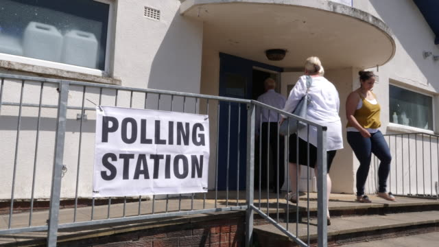 4k: polling station sign / banner - people going to vote in elections, wide shot - democracy stock videos and b-roll footage