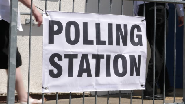 4k: polling station sign / banner - people walking to vote in elections - election stock videos and b-roll footage