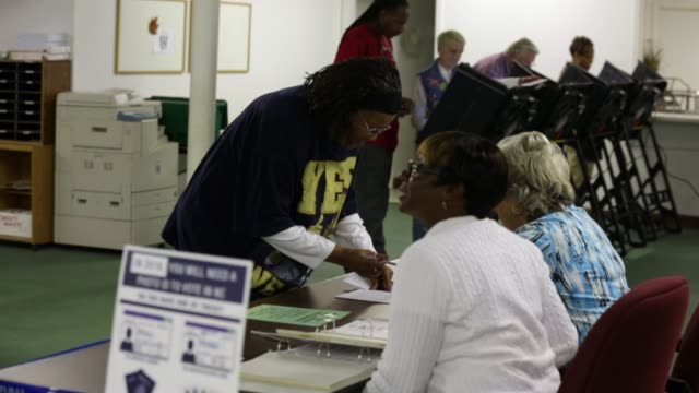 polling workers help voters to check in prior to casting their ballots on election day greensboro nc november 4 2014 - midterm election stock videos & royalty-free footage
