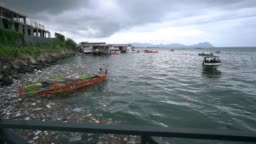 Polluted fishing port in Malaysia, filled with plastic bottles and bags.