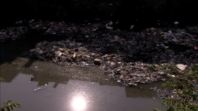A polluted river flows in front of the slums of Dharavi. Available in HD.