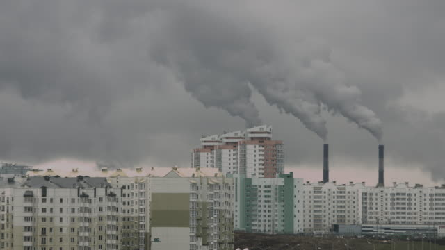 Polluting power plant pipes with heavy clouds of wastes near residential area