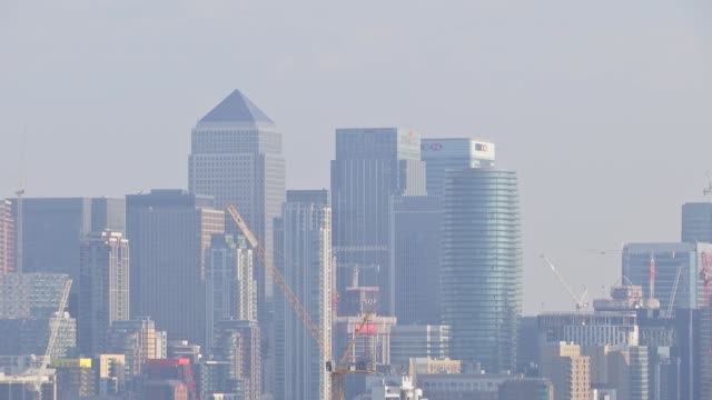 london ext pollution seen in london skyline / canary wharf skyscrapers / chimney tops / city of london skyscrapers / tree branch / polluted cityscape - cityscape stock videos & royalty-free footage