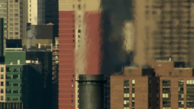 pollution rises from a power plant smokestack on the south side of manhattan. - 発電所点の映像素材/bロール