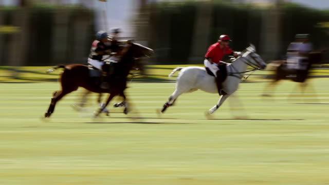 WS TS Polo player in red jersey fast galloping across field and hitting fast moving ball / Indio, California, USA
