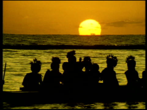 polynesian and south pacific tribal people wearing traditional costume, paddle slowly along in canoe silhouetted by sunset on horizon of ocean - south pacific ocean stock videos & royalty-free footage