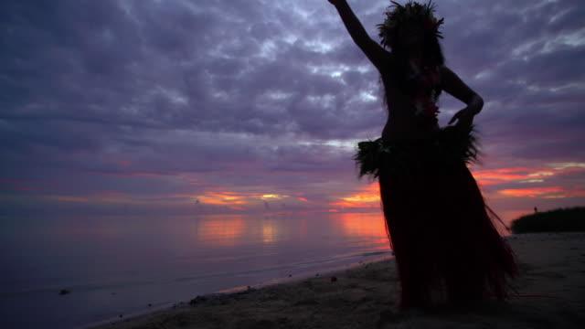vidéos et rushes de polynesian female hula dancer performing on sunset beach - grâce