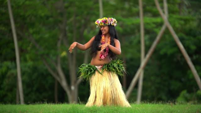 vidéos et rushes de polynesian girl dancer in grass skirt and headdress - grâce